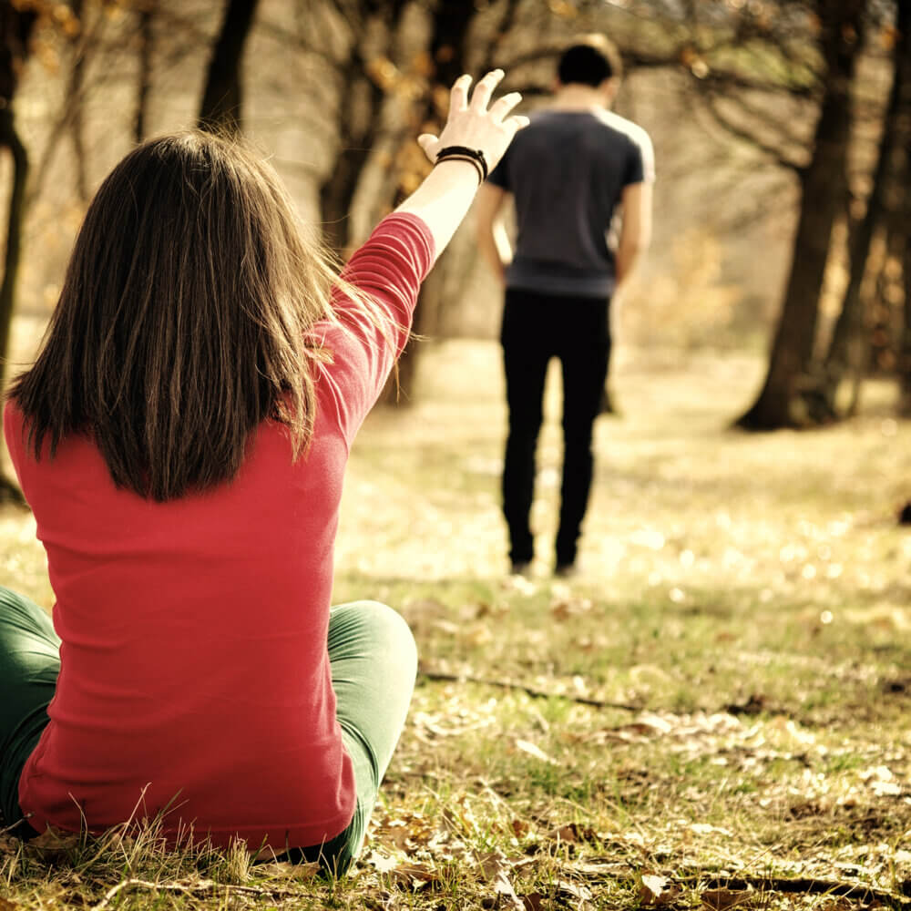 woman reaching out to man to come back after an argument